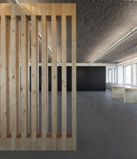 This concrete-lined office features slatted timber panels to break up spaces.