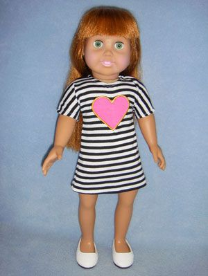 """Black & White Striped Knit Dress w/pink heart has short sleeves & Velcro fastener down the back. Fits 18"""" girl dolls such as Springfield Collection & Magic Attic. Shown with 2 3/4"""" White Slip On Shoes (66486) (not included)."""
