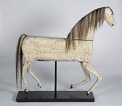 Remarkable, Perhaps Unique, Articulated Carved Folk Art Horse of Substantial ScaleNortheast America, ca. 4th quarter, 19th century. Carved from pine, decorated with oyster white paint body with blue and black dappling. Original horse-hair mane and tail, tack eyes, and horse shoes made of tin. Likely made as a wind up toy or velocipede with moveable head, tail, ears, and legs.