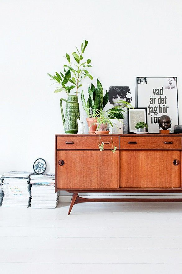 Bright wooden cabinets, white walls, potted plants + black + white framed designs