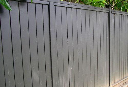 A tall privacy ensuring wooden fence.