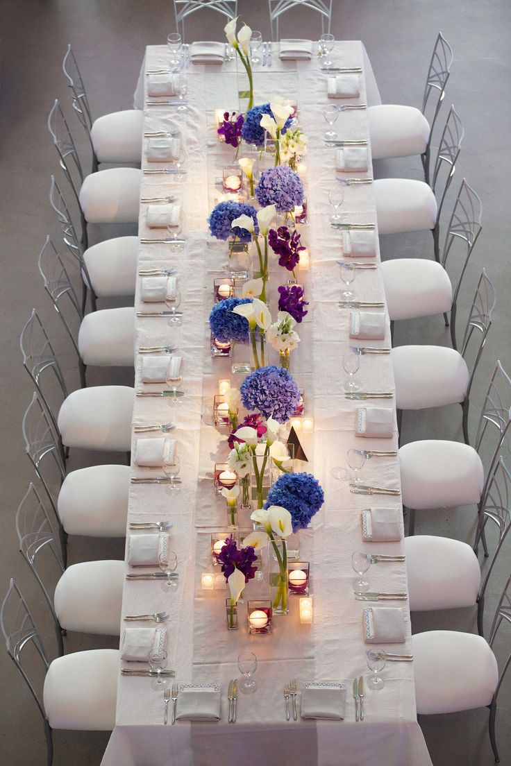 Wedding guests sat at long, rectangular tables swathed in crisp white linens and surrounded by silver-backed chairs. A silver runner topped with arrangements of purple orchids, blue hydrangeas, and white calla lilies ran the length of the table. #tabledecor #weddingreception Photography: Bob & Dawn Davis Photography. Read More: https://www.insideweddings.com/weddings/modern-purple-blue-white-wedding-at-contemporary-chicago-venue/541/