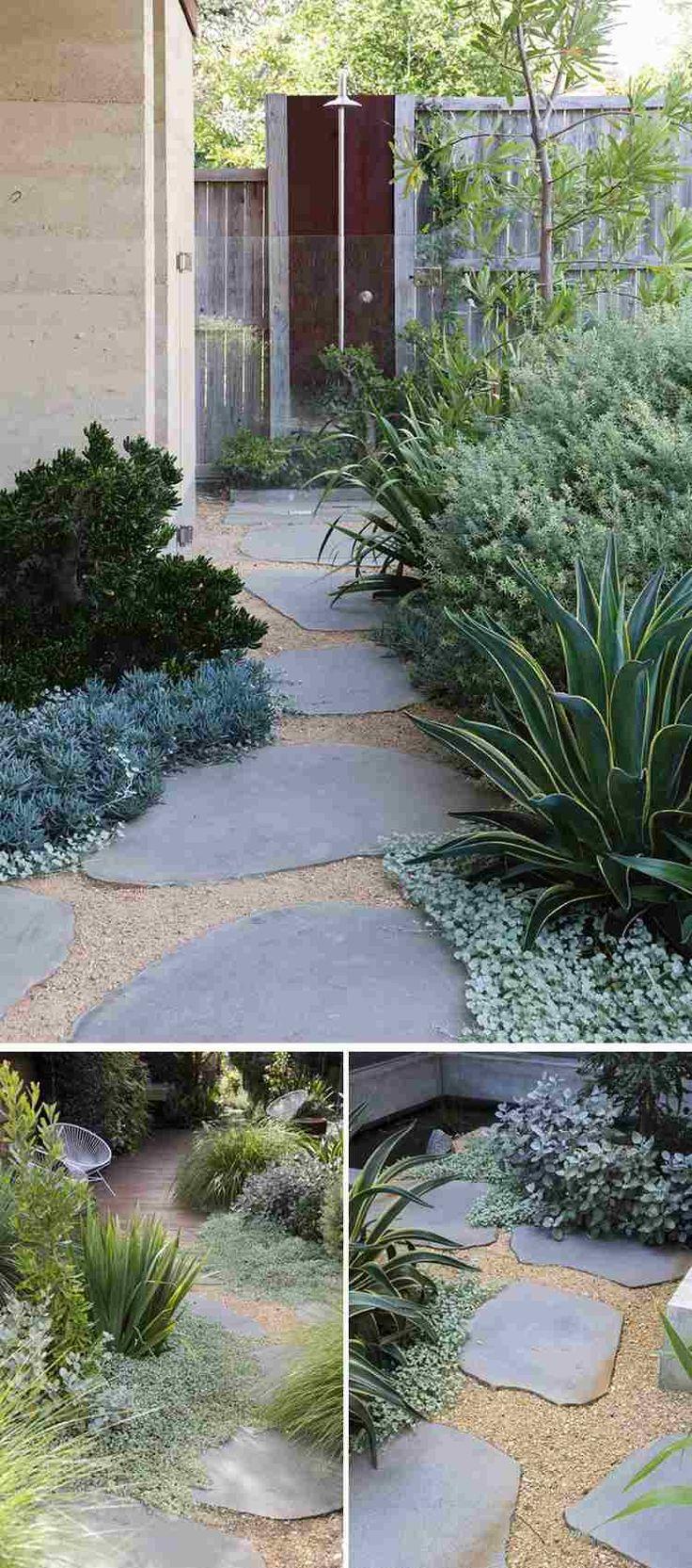 un chemin de jardin en pas japonais en ardoise grise emmène jusqu'à la douche de jardin