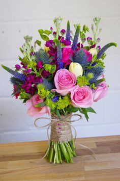 Bright, bold bridal bouquet! This one featured purple-blue Veronica, natural blue Thistle, hot pink Stock, various pink Roses, cream Tulips, and lime green Bupleurum greenery.