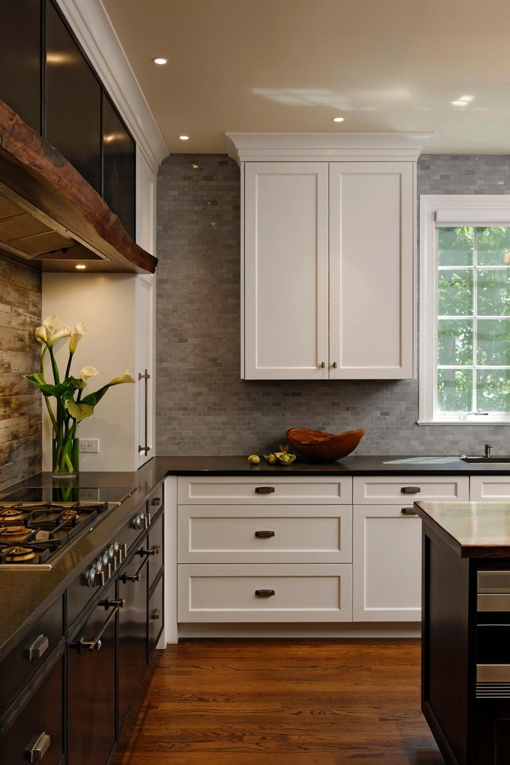 Cool blue-gray marble tile extends from the quartz countertop to the ceiling in this pretty, transitional kitchen. Metal cabinets surround the cooktop, creating a high-contrast focal point. The custom range hood is made from live-edge walnut.