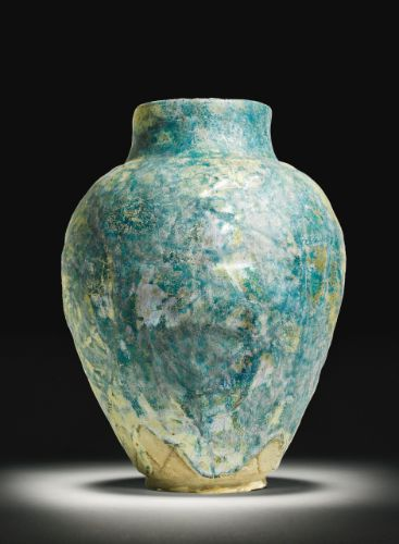 A Raqqa turquoise glazed ovoid jar, Syria, first half 13th Century the ovoid body with straight neck and rim, decorated with a turquoise glaze across a moulded surface design 32.5cm.