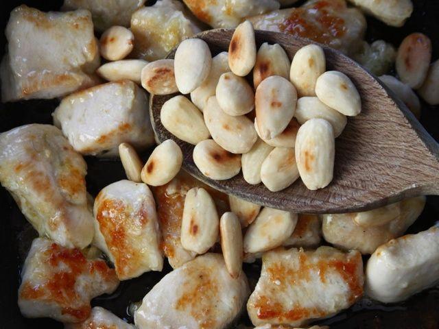 POLLO ALLE MANDORLE 4/5 - Scolate i cubetti di pollo e fateli rosolare in un tegame con l' olio caldo facendoli dorare leggermente; aggiungete le mandorle, fatele insaporire brevemente, scolate gli ingredienti e teneteli da parte.