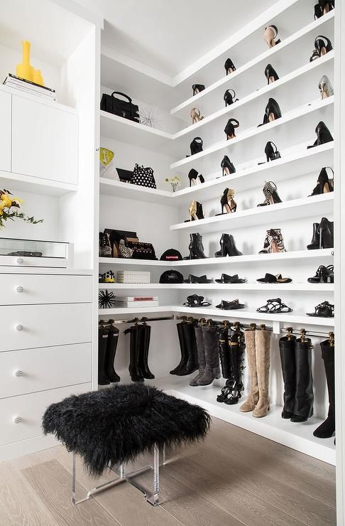 Chic walk in closet features stacked wraparound shelves filled shoes as well as a shelf dedicated to boots fitted with hooks.