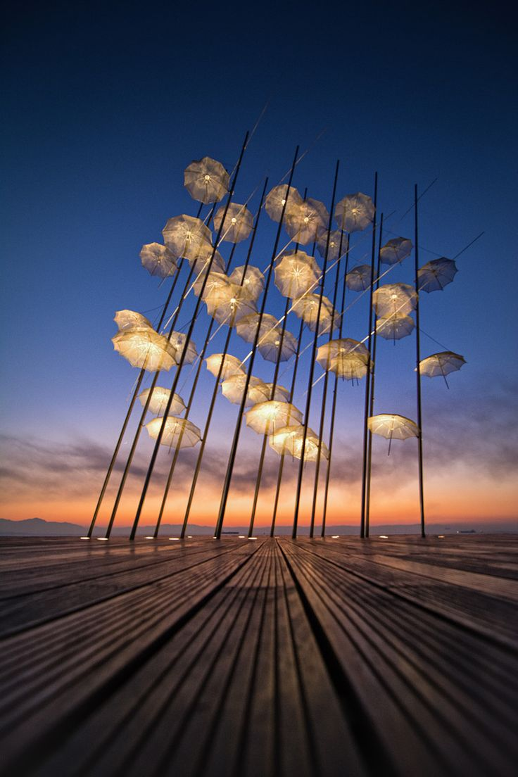 Thessaloniki, Greece. An umbrella art installation by George Zongolopoulos towers over the cafe-lined waterfront of this lively seaside city.