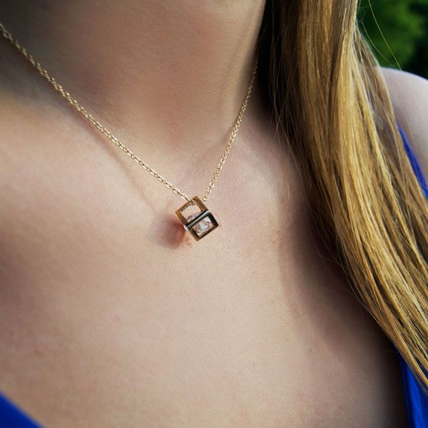 What a unique necklace! This gold chained geometric cube necklace features an imitation gemstone inside!