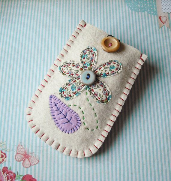100% wool felt phone case with appliqued and hand embroidered pretty flower design on the front. The case is fully lined with patterned cotton and has a wooden button and elastic loop for closure. A perfect home for an iPod, iPhone, Blackberry, mobile phone, MP3 player or digital camera.....Made with super thick felt to keep your gadget safe and scratch free.