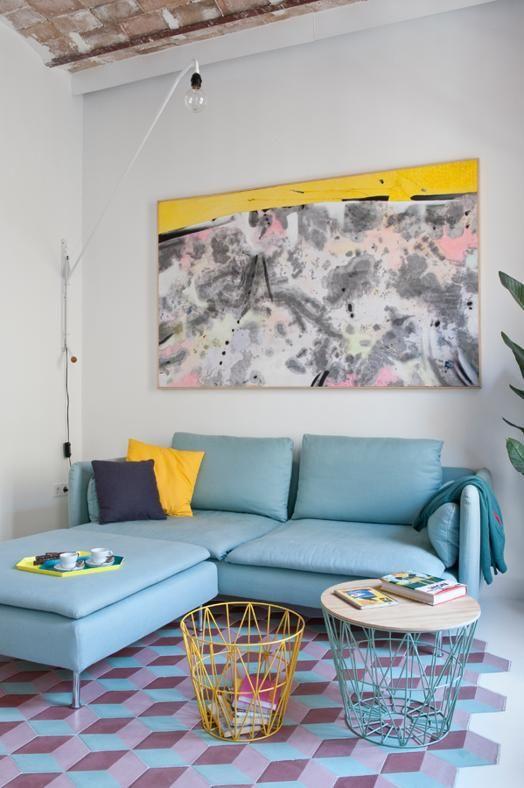 100 MQ NELL'EIXAMPLE: LA ZONA LOUNGE Vibranti note gialle colorano la zona lounge. Attorno al divano grigio a penisola Söderhamn di Ikea, tavolini in rete metallica di Ferm Living e lampada da parete Potence di Vitra (design C.& R. Eames) verniciata bianca.