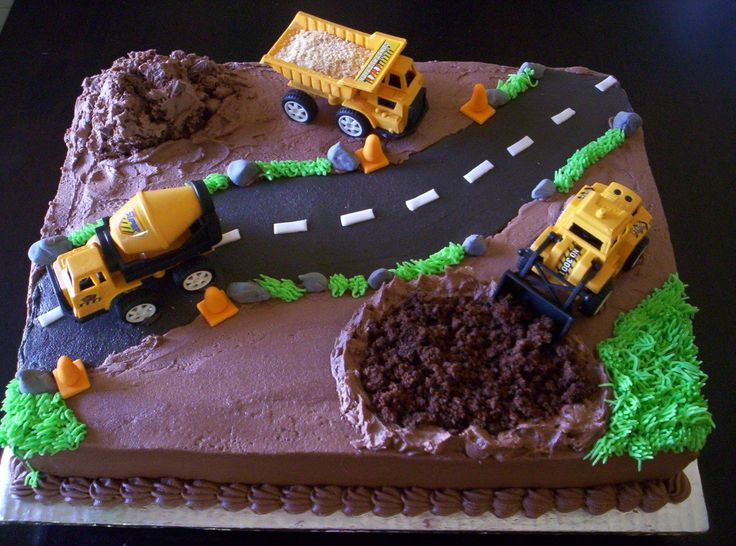 CONSTRUCTION CAKE - Chocolate cake with BC frosting, construction vehicles supplied by the mom, crushed biscuits in the dump truck and BC frosting for grass....fondant rocks
