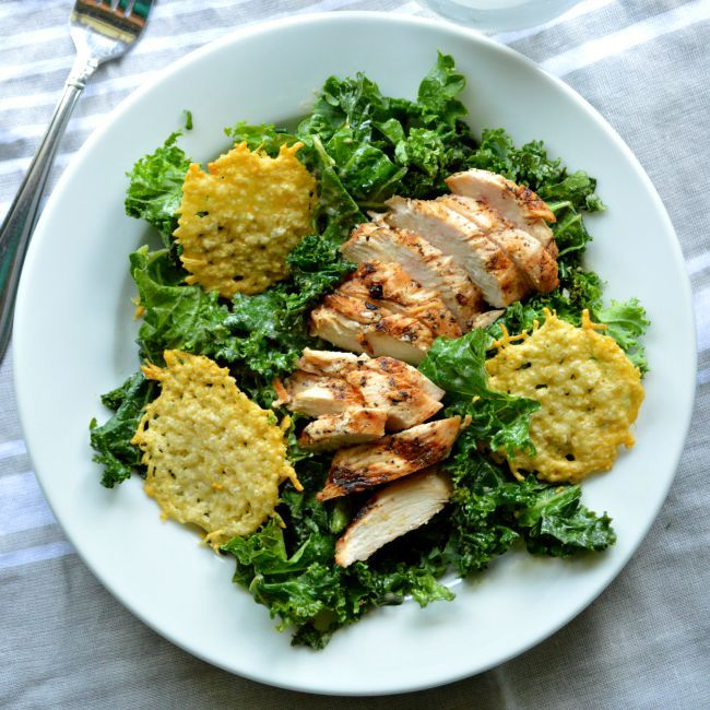 Make this easy copycat recipe at home in less than 30 minutes! This Power Kale Caesar Salad recipe is topped with grilled chicken and Parmesan crisps. Love!
