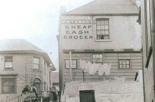 "The rear of the Susannah Place terrace,Cumberland Place at The Rocks of Sydney (in detail). The ""cash grocer"" on the corner of Susannah Place at 64 Gloucester St was serving local customers for over 90 years. During this time there were 12 shopkeepers who lived onsite with their families.The two we know most about are George Hill,who ran the shop from 1879 –1890, and Clara and Hugo Youngeins,who ran the shop from 1904-1930.  •Mitchell Library,State Library of NSW•"