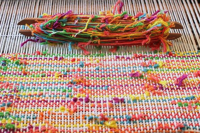 Weaving up some fun fabric out of hand-tied cotton scrap yarn in bright colors; it's meant to be turned into pillow covers and similar. It'll be interesting to see how it washes up- I&#…