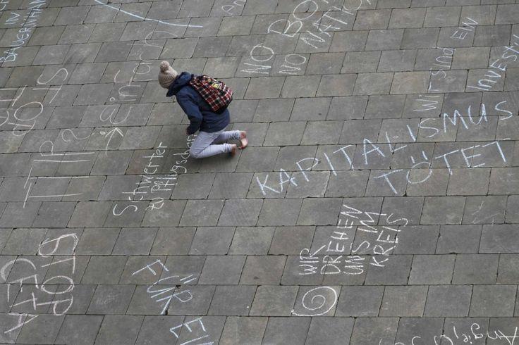 Eine Demonstrantin schreibt Protest-Slogans gegen TTIP auf den Boden. Im Vorfeld von US-Präsident Barack Obamas Besuch in Hannover protestierten Zehntausende gegen das Handelsabkommen (© Reuters/Kai Pfaffenbach, 23.04.2016).