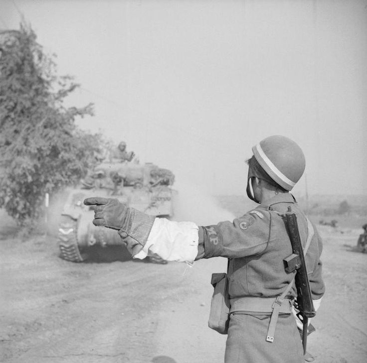 THE POLISH ARMY IN THE NORMANDY CAMPAIGN, 1944 - Military Policeman of the Traffic Regulation Squadron (1st Polish Armoured Division) regulating the traffic at the beginning of the Operation 'Totalise', south of Caen, 8 August 1944.