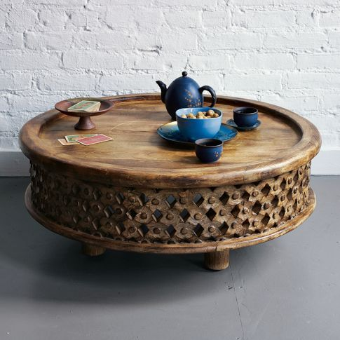 Part sculpture, part table, all artisanal. Craftspeople in Jaipur, India, hand carved the delicate rosettes on this low-lying solid mango wood table, which takes its original inspiration from a ceremonial stool used by Bamileke royalty in the African country of Cameroon.    Round is good, no corners to bang into.