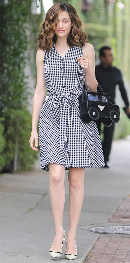 Emmy Rossum pulled off gingham—one of spring's hottest prints—in a sleeveless Aqua gingham shirtdress, complete with a playful car-motif novelty purse and neutral pumps.
