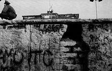 Muro de Berlín - Wikipedia- Porción del Muro de Berlín, en parte destruida, vista desde el lado occidental, con un guardia fronterizo y la Puerta de Brandeburgo al fondo, noviembre de 1989.