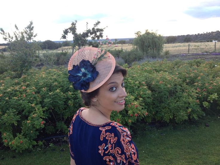 Una invitada con el elegante tocado de base de sinamay ondulada coral y flor en azul marino