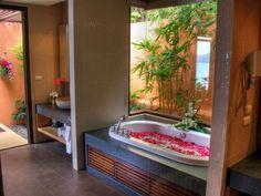 """baignoire avec tablier en bois et pierre, vasque ronde en pierre et vue sur le jardin """"vert"""""""