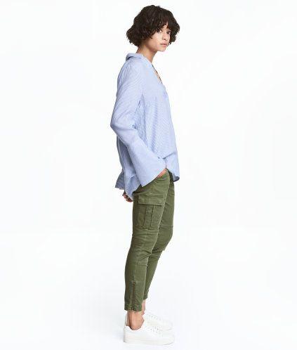 Khakigrün. Cargohose aus stretchigem Baumwolltwill. Die Hose hat Seitentaschen sowie Bein- und Potaschen mit Patte und Druckknopf. Ziersteppungen auf den