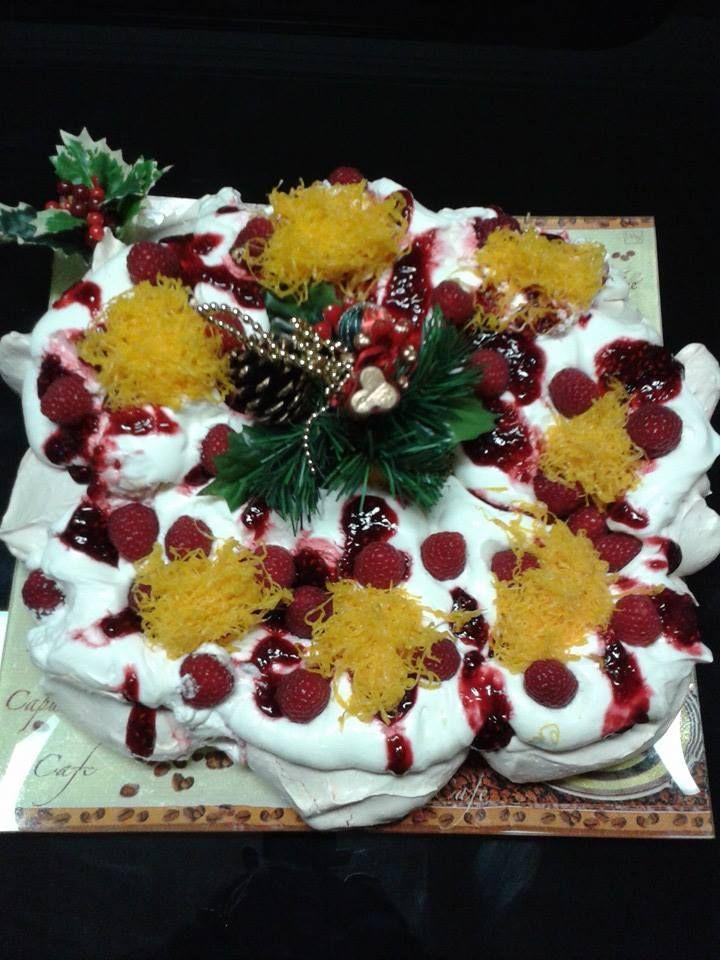 Christmas Pavlova em forma de coroa, decorada com chantilly, coulis de framboesa, framboesas e fios de ovos