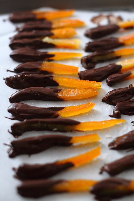 Chocolate-Dipped Candied Orange Peel Peel an orange, make sure to remove the all of the white pith (which is bitter). Slice the peel into strips, and blanch the strips in water 3 times. Boil in a simple syrup until softened, and lay them to dry on parchment. Once dried they can be dipped in melted chocolate, or just eaten straight. #chocolates #sweet #yummy #delicious #food #chocolaterecipes #choco