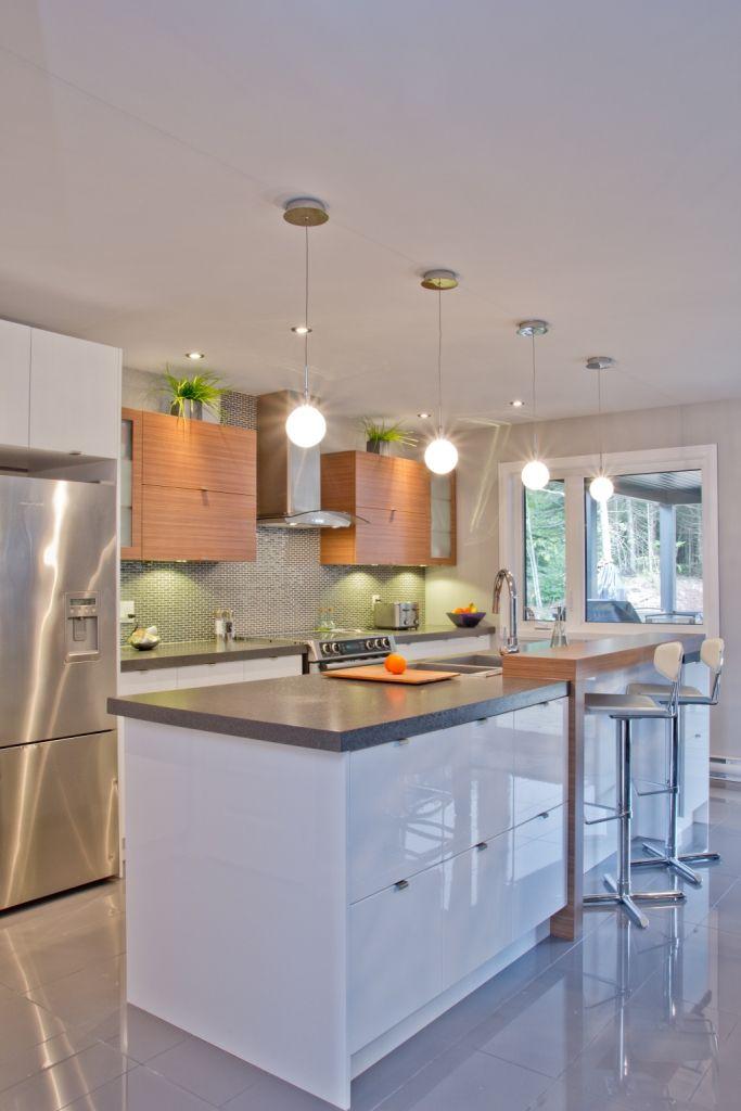 Nous retrouvons dans cette cuisine l'agencement de 2 tons. L'îlot et les armoires de la cuisine de style panneau plat ont été réalisés en thermoplastiques lustré et en mélamine. Le tout est harmonisé avec un comptoir en stratifié.