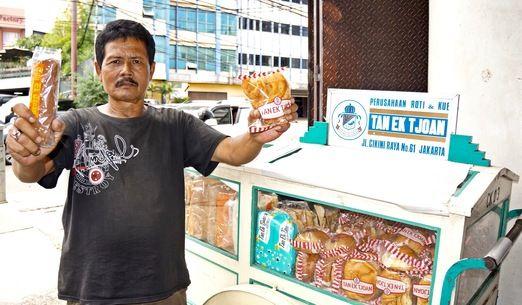 Selling traditionally: a Tan Ek Tjoan bread seller using a bicycle cart shows customer favorites roti gambang on his rig...