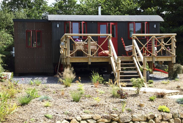 "Located near Watergate Bay in Cornwall, England a Wild West-themed wagon-style dwelling, is available to rent through Unique Homestays. Decorated with a ""saloon chic"" aesthetica . After a day riding horses on the nearby beach, relax with a glass of wine while sitting in a rocking chair on the lantern-lit front porch. Rental rates are about $800 for a three-night stay.  Look inside the Sundance."