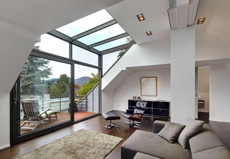 Grenier avec lucarne en verre: salon appuyé contre un bureau d'architecture