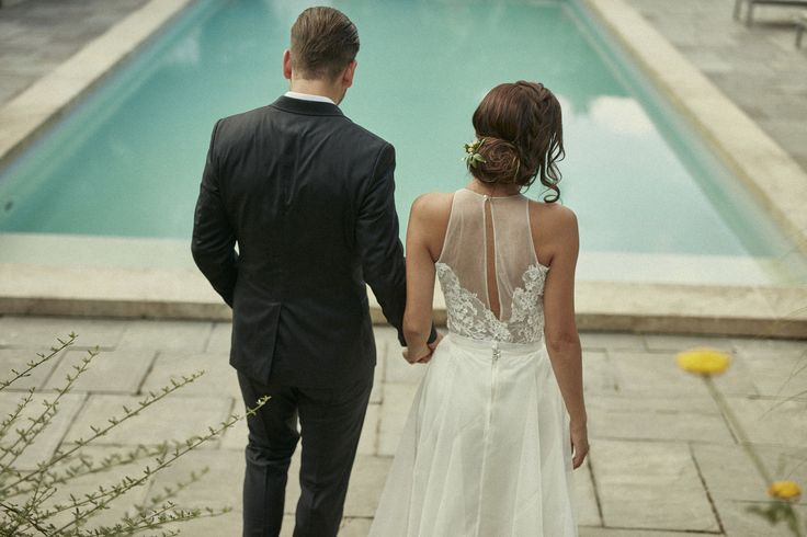 Hand in hand by the pool. Romantic wedding moments.
