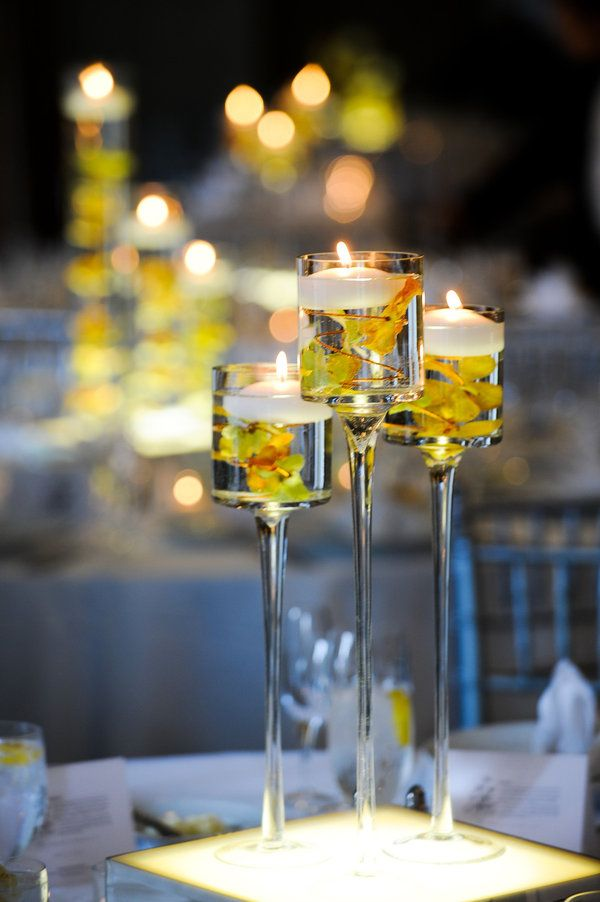 Centros de mesa con copas altas y velas flotantes.