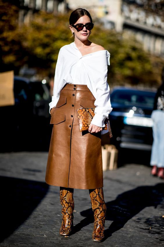 17969d366c1db6 White button down shirt worn off the shoulder with midi length brown  leather skirt with pockets and button detail. Brown snake print leather  knee boots and ...