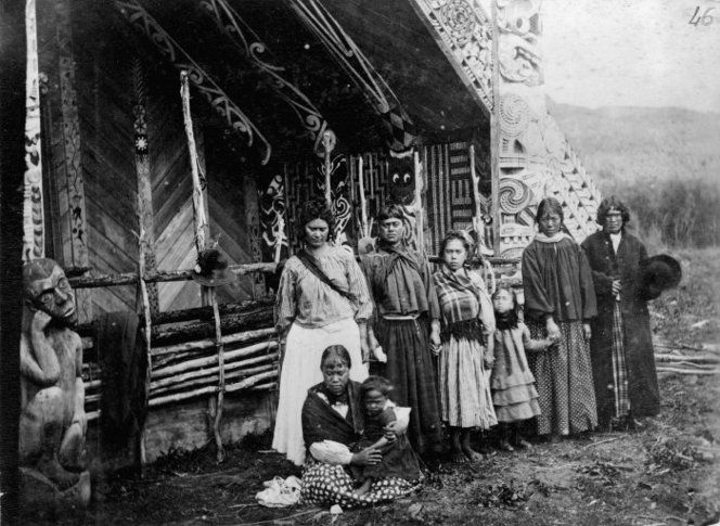 Unidentified group alongside the Te Tokanganui-A-Noho meeting house in Te Kuiti, 1884. #Maori
