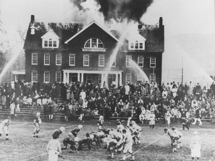 1965  A high school football game goes on as a fire rages on at a boarding school in Northfield, Massachusetts.