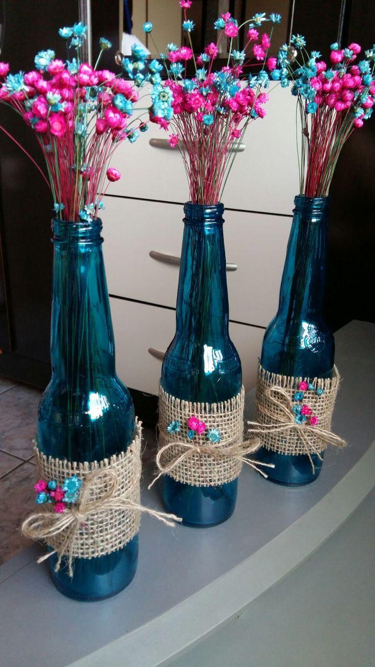 """Fiz para decoração do chá de panela da minha irmã. Garrafas de cerveja transparentes pintadas com verniz vitral na cor azul turqueza. Flores """"sempre viva"""" e tecido para decorar."""