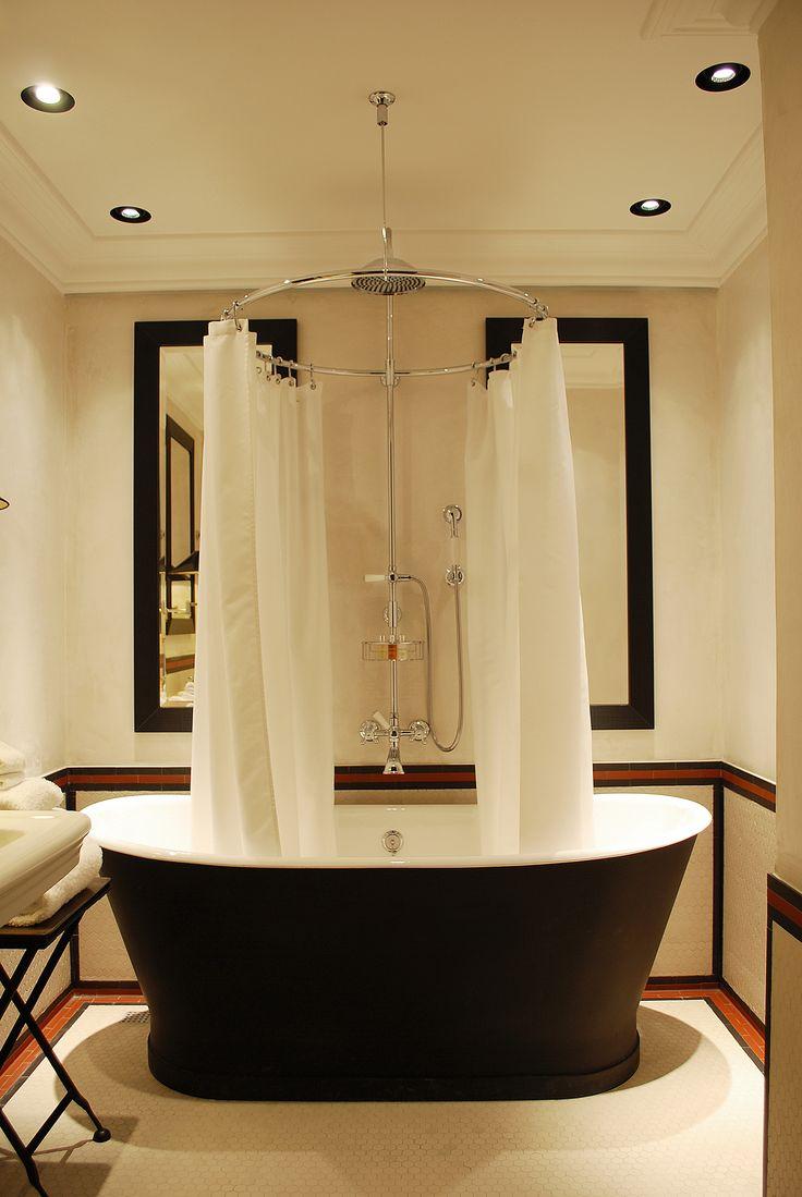 Stunning Bathroom...Love the Striking Black Bathtub & the circular shower curtain rod.