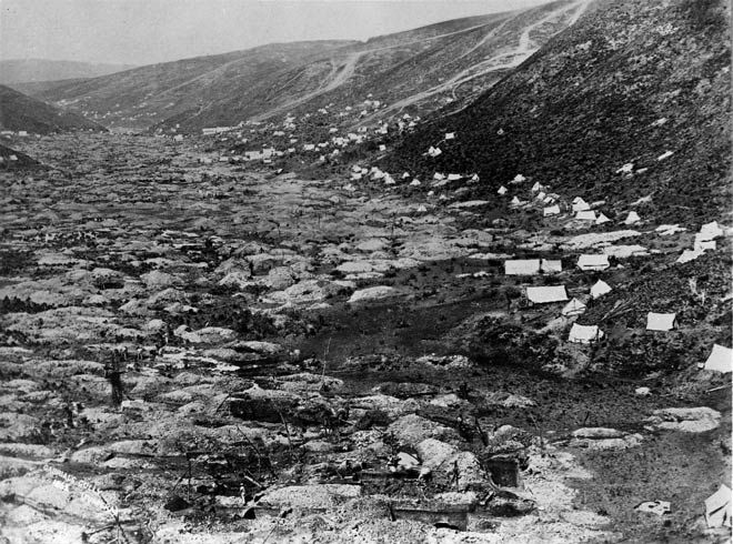 Gabriels Gully:Taken in 1862, the year after Gabriel Read discovered gold, this photograph shows a moonscape of pitted earth. Miners dug down to 4 metres and raised up the gold-bearing gravels using devices called whips – a counterbalanced mānuka pole with a bucket on the end. The miners' calico tents hug the sides of the hill away from the claims. It was Read's discovery that led to the great Otago gold rushes of the 1860s.