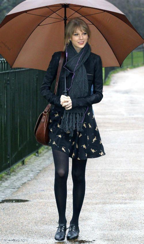 Taylor Swift enfrenta um dia chuvoso com um look superestiloso! Destaque para a jaqueta tipo perfecto e a estampa fofa do vestido!