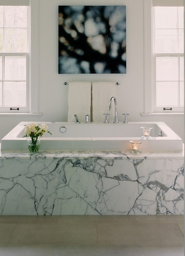 Encased in Statuario marble, the bathtub makes a dramatic statement.