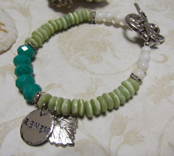RENEW stamped word charm bracelet with silver leaf charm. Teal, green, and white with sparkling rhinestone spacers. Toggle clasp closure has a