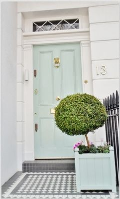 A pale blue paint with gold accents freshens any front door. Topiaries add color.