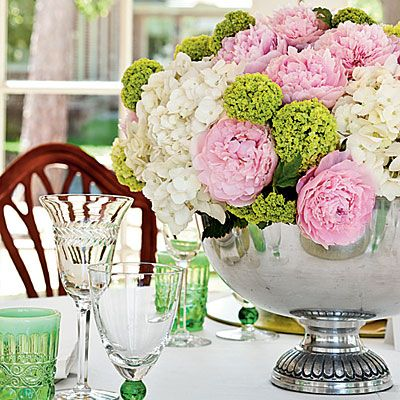 Pink peonies, white hydrangeas, and green viburnums in a silver punch bowl