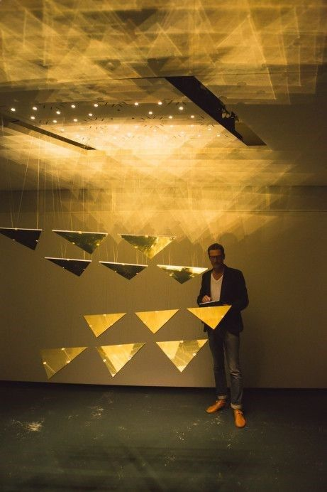 kinetic installation composed of triangular mirrors that move vertically and rotate around two axes in a complex choreography of flowing three-dimensional structures. Their physical movement is enhanced with ceiling lighting and an interplay between the reflective triangles and the dark, overlapping shadows they cast on the floor.   JOACHIM SATER