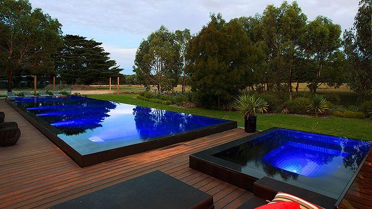 Raised black tile pool and spa with infinity edge on all sides. Very sleek. Pinned to Pool Design by Darin Bradbury.