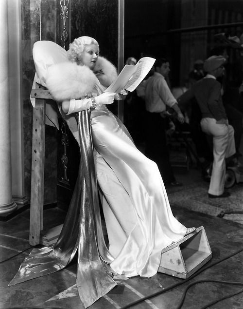 """Jean Harlow on the set of """"Dinner at Eight"""" (1933). Her white satin gown by Adrian was cut on the bias and so form fitting she could not sit down in it, so MGM constructed this """"reclining board"""" so she could rest between takes."""